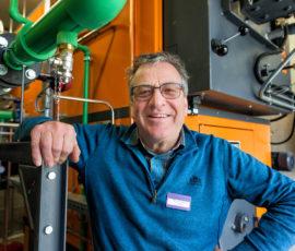 Piet van der Heijden bij de houtgestookte ketel van Verpleeghuis Oranje Nassau's Oord.