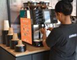 Medewerker zet koffie met apparaat